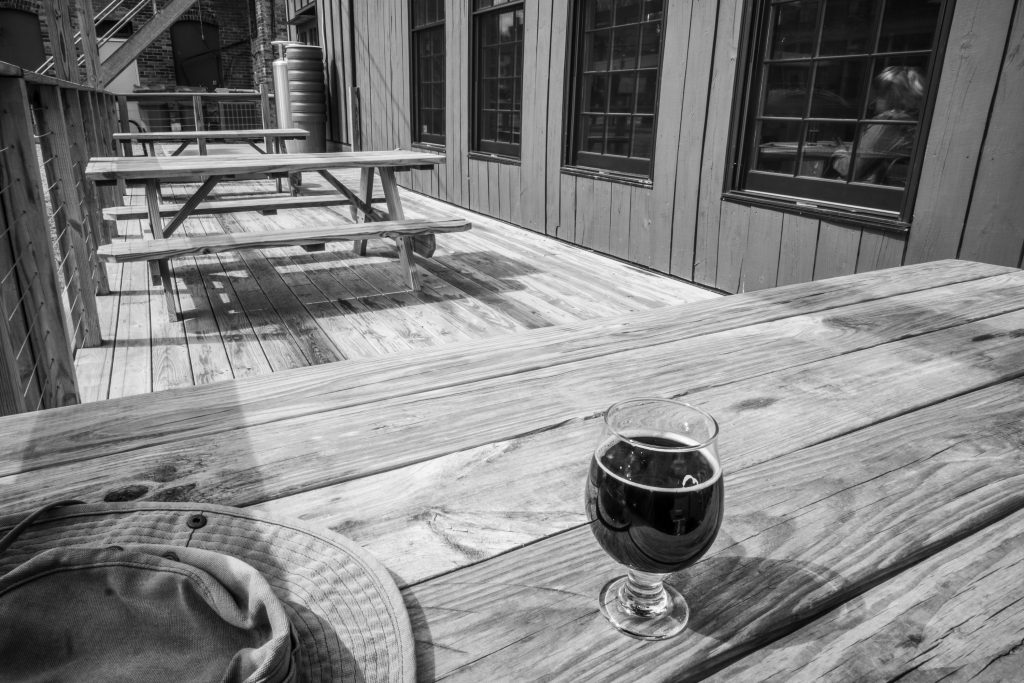 a deck with three picnic tables. A hat and a glass of dark beer on the nearest table