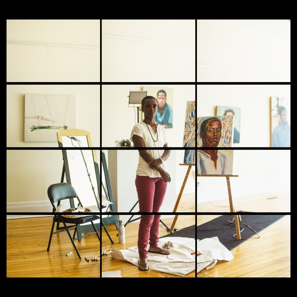 young black woman painter in gallery with her paintings