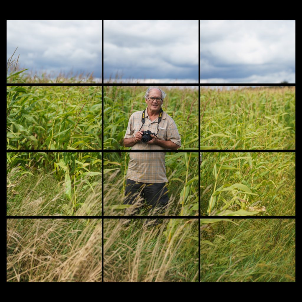 white male standing in a corn field with a camera