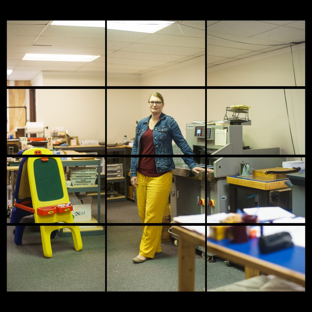 white woman in bright yellow pants and blue denim jacket with office machines and child's painting easel