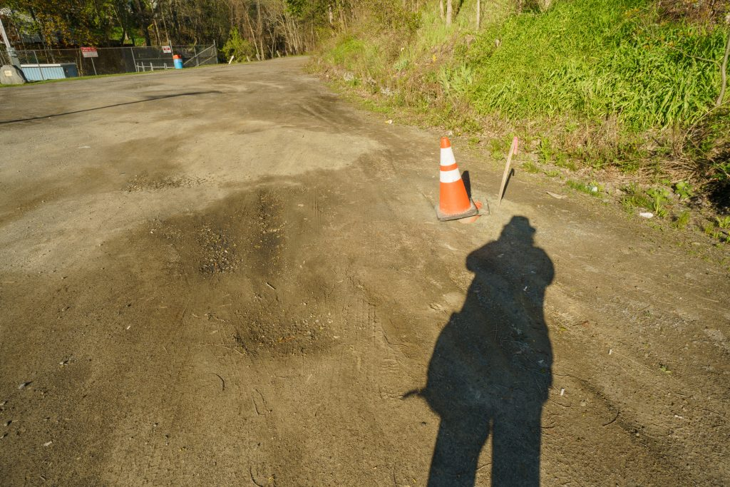 traffic cone, survey stake, shadow of photographer, dirt lot