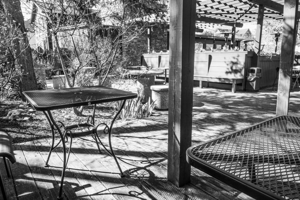 a restaurants patio, wire tables, sun through the trees