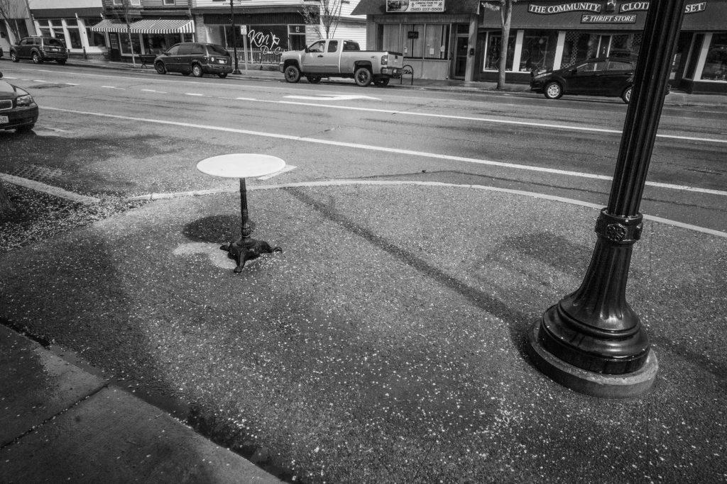 a small empty table on a sidewalk near a street