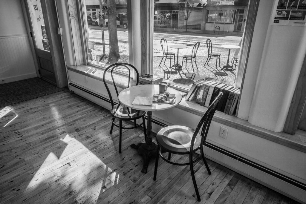 view from café out window to sidewalk with tables and chairs
