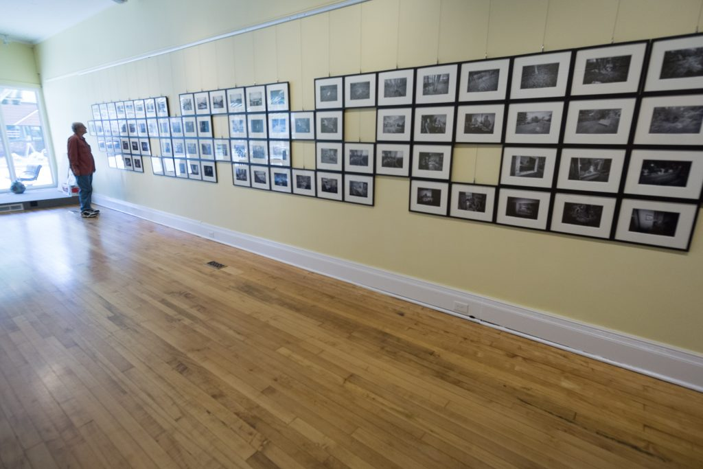 male in art gallery with a wall of photographs