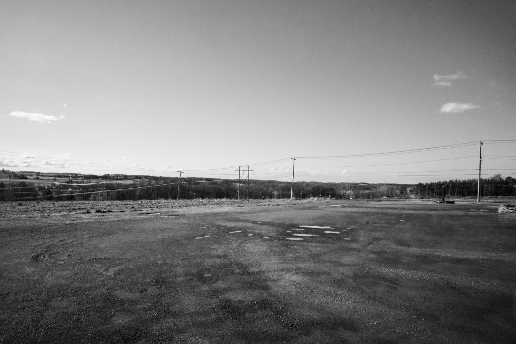 dirt parking lot after a rain, utility lines on the horizon