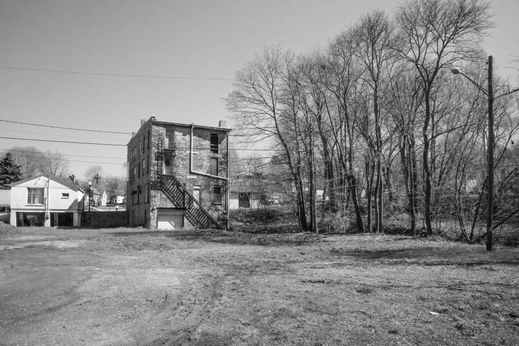 empty dirt lot, back of old brick building, line of trees
