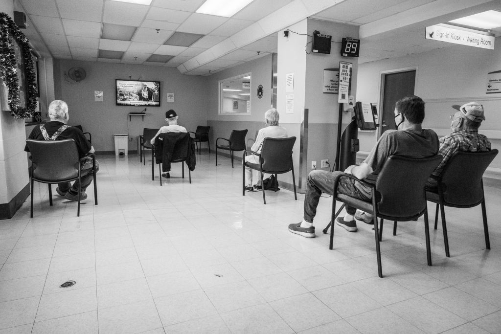 five people sitting in a waiting room watching TV